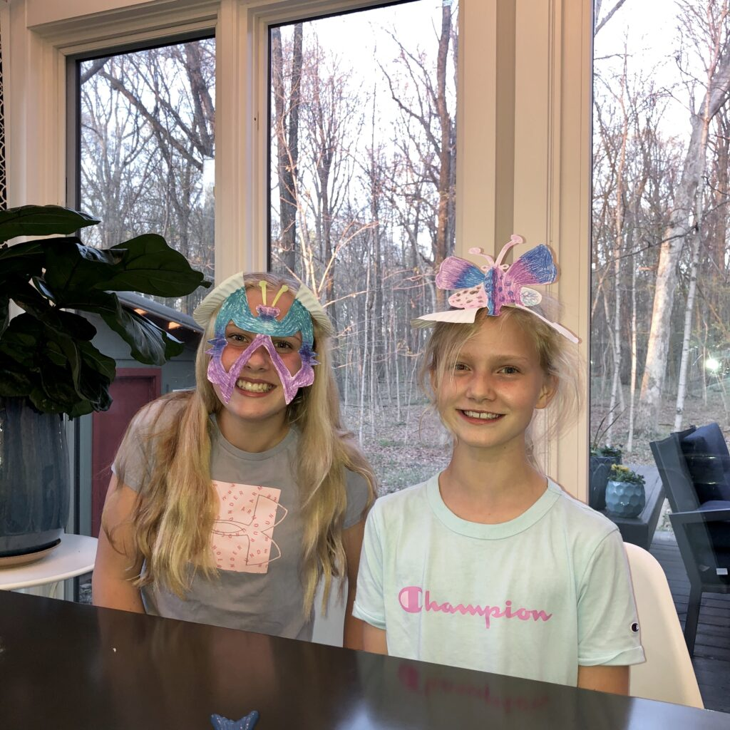 two girls wearing a bug mask and a bug hat